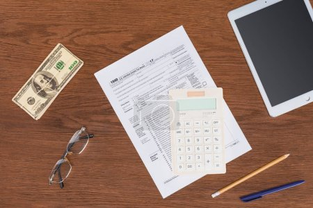 top view of tax form, calculator and dollar banknote on wooden desk at workplace