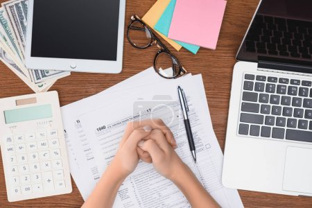 cropped view of woman with folded hands sitting at desk with tax forms and digital devices