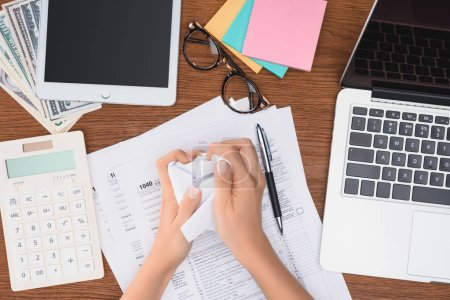 cropped view of woman holding crumpled paper ball at desk with tax forms and digital devices