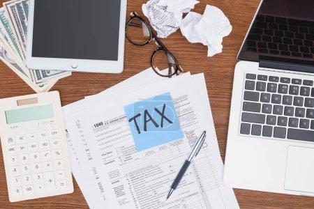 """Photo pour Vue en haut des formulaires fiscaux, des appareils numériques et de la carte bleue avec mot """"fiscal"""" sur le bureau - image libre de droit"""