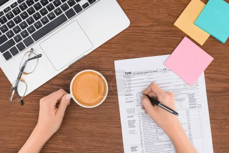 cropped view of woman holding coffee cup and filling tax form at workplace