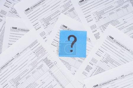 Photo pour Vue du haut du point d'interrogation sur la carte bleue avec des formulaires fiscaux sur fond - image libre de droit