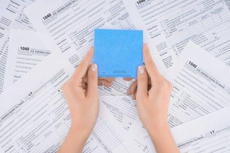 Photo pour Vue de femme tenant vide carte bleue avec formulaires fiscaux sur fond de rognée - image libre de droit