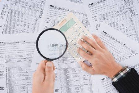 Photo pour Vue recadrée de l'homme tenant une loupe et utilisant une calculatrice avec des formulaires fiscaux sur fond - image libre de droit