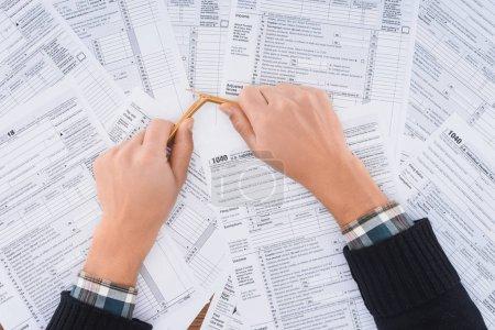 Photo pour Vue recadrée de l'homme stressé crayon cassant avec des formulaires fiscaux sur fond - image libre de droit