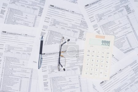 Photo pour Vue du haut de la calculatrice, stylo et lunettes avec des formulaires d'impôt sur le fond - image libre de droit