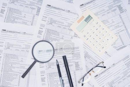 Photo pour Vue du haut de la calculatrice, loupe et papeterie avec formulaires fiscaux sur fond - image libre de droit