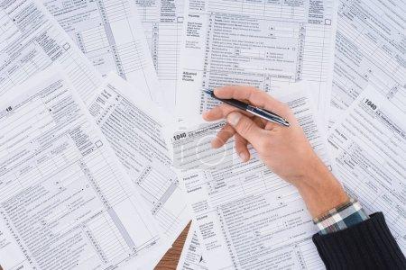 Photo pour Vue partielle de l'homme tenant un stylo et remplissant les formulaires fiscaux avec espace de copie - image libre de droit