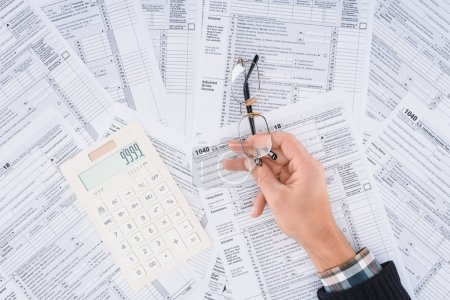 cropped view of man holding glasses with calculator and tax forms on background