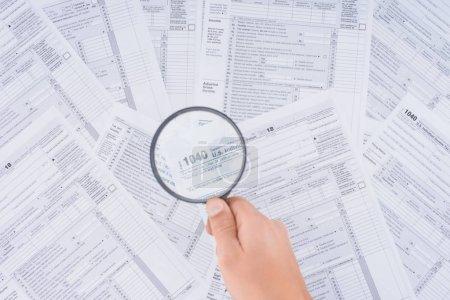 Photo pour Vue recadrée de l'homme tenant une loupe sur des formulaires fiscaux - image libre de droit