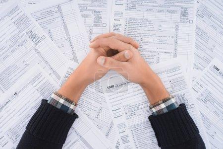 Photo pour Vue recadrée de l'homme avec les mains pliées sur le fond avec des formulaires fiscaux - image libre de droit