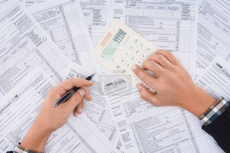 Photo pour Vue recadrée de l'homme remplissant des formulaires fiscaux et utilisant une calculatrice - image libre de droit