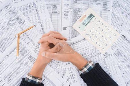 Photo pour Vue recadrée de l'homme avec les mains pliées, crayon cassé et calculatrice avec des formulaires fiscaux sur fond - image libre de droit