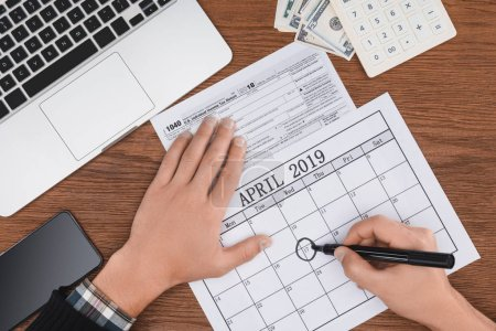 cropped view of man marking april 17 date in calendar on wooden desk