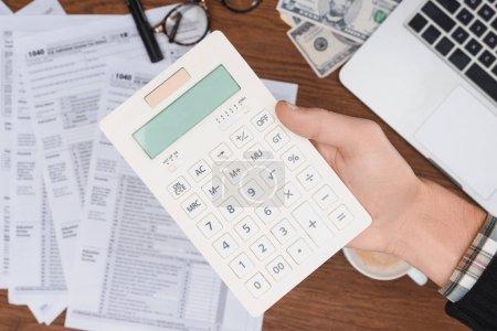 Photo pour Foyer sélectif de l'homme à l'aide d'une calculatrice avec des formulaires fiscaux sur fond - image libre de droit