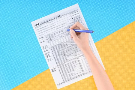 cropped view of woman filling tax form on blue and yellow background