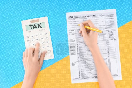 cropped view of woman using calculator with word 'tax' and filling tax form on blue and yellow background