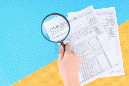 Photo pour Vue recadrée d'une femme tenant une loupe sur des formulaires fiscaux sur fond bleu et jaune - image libre de droit