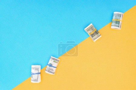 Foto de Vista superior de dinero rueda sobre fondo azul y amarillo con espacio de copia - Imagen libre de derechos