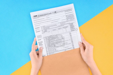 Photo for Cropped view of woman holding tax form on blue and yellow background - Royalty Free Image
