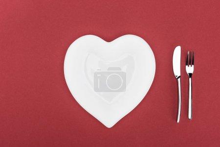 Photo pour Vue du cœur en forme de plaque et couverts isolés sur la notion de jour rouge, st Valentin - image libre de droit