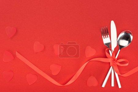 Photo pour Vue surélevée des couverts enveloppés par un ruban festif près des symboles du cœur isolé sur le rouge, concept de Saint-Valentin - image libre de droit