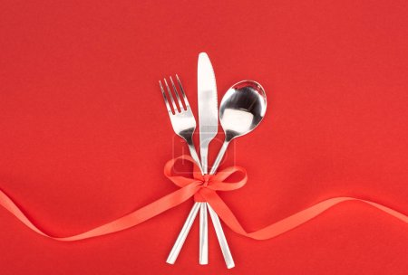 flat lay with fork, knife and spoon wrapped by red festive ribbon isolated on red, st valentine day concept