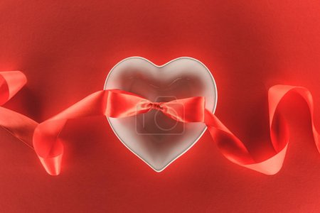 elevated view of heart symbol and festive ribbon isolated on red, st valentine day concept