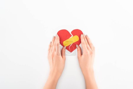 cropped shot of woman holding broken red heart with medical patch symbol isolated on white, st valentine day concept