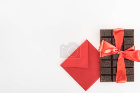 Photo for View from above of envelope and delicious chocolate wrapped by festive ribbon isolated on white, st valentine day concept - Royalty Free Image