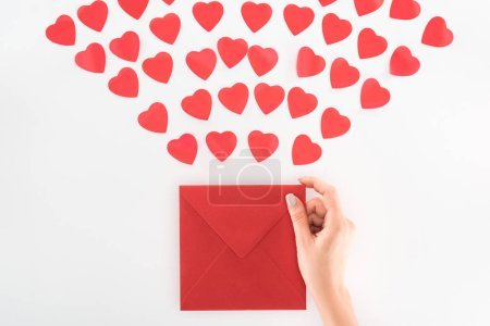 Photo for Partial view of woman holding envelop under dozen red heart symbols isolated on white, st valentine day concept - Royalty Free Image