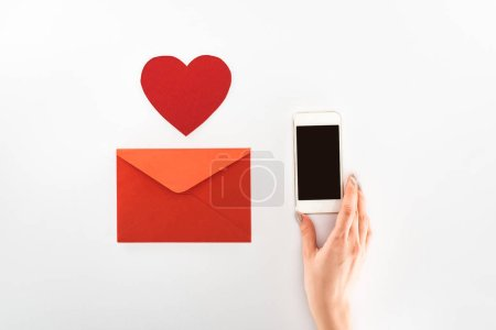 Photo for Cropped image of woman holding smartphone with blank screen near heart symbol and red envelope isolated on white, st valentine day concept - Royalty Free Image
