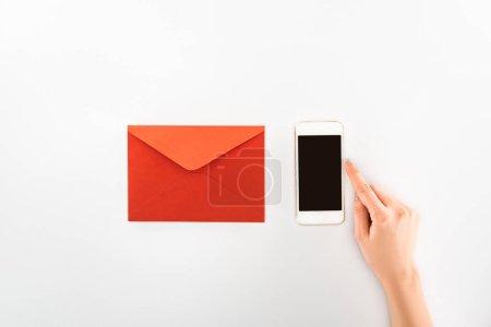 Foto de Vista parcial de mujer smartphone con pantalla en blanco junto a la envolvente roja aislado en blanco, el concepto de día de San Valentín - Imagen libre de derechos