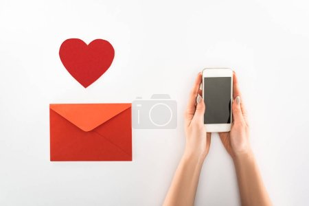 Photo for Partial view of woman holding smartphone with blank screen near heart symbol and red envelope isolated on white, st valentine day concept - Royalty Free Image