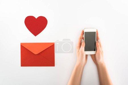 Foto de Vista parcial de mujer smartphone con pantalla en blanco cerca del símbolo del corazón y envolvente rojo aislado en blanco, concepto de día de San Valentín st - Imagen libre de derechos