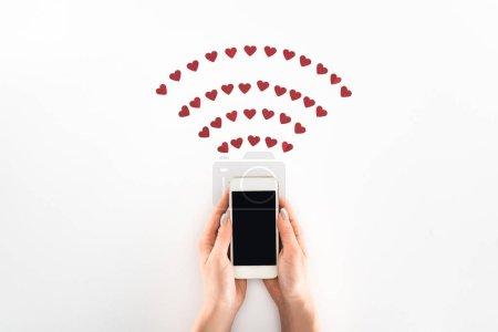 Foto de Vista parcial de mujer con smartphone con pantalla en blanco con el slmbolo de corazón rojo aislado en blanco, el concepto de día de San Valentín - Imagen libre de derechos