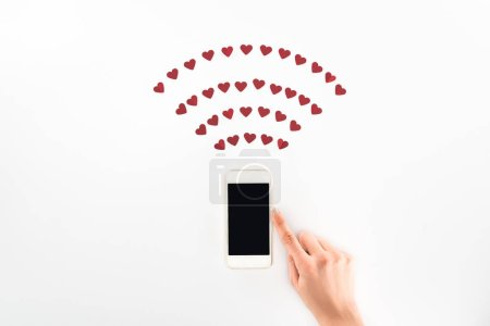 Photo pour Image recadrée de femme à l'aide de smartphone avec un écran blanc sous les symboles coeur rouge isolé sur blanc, concept jour de st Valentin - image libre de droit
