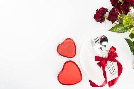 Foto de Vista superior de la placa y cubiertos envuelto por la cinta festiva, en forma de corazón actuales cajas y bouquet de rosas rojo aislado en blanco, el concepto de día de San Valentín - Imagen libre de derechos
