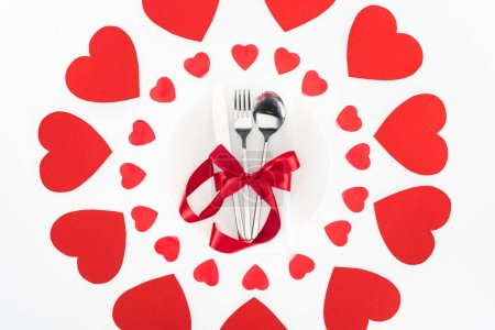 elevated view of cutlery wrapped by red festive ribbon surrounded by heart symbols isolated on white, st valentine day concept