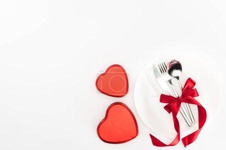Photo pour Vue de dessus de plaque avec coutellerie enveloppé de ruban festif près de coeur en forme de boîtes présents isolés sur blanc, concept jour de st Valentin - image libre de droit