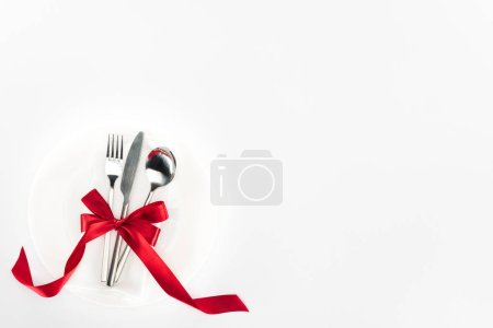 Photo for Elevated view of fork, knife and spoon wrapped by red festive bow on plate isolated on white, st valentine day concept - Royalty Free Image