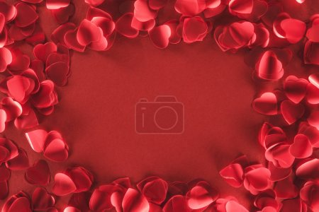 top view of decorative heart shaped petals on red background, valentines day concept
