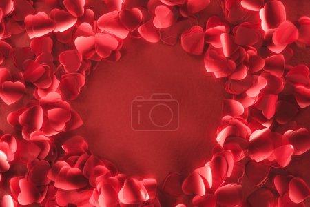 Photo pour Vue de dessus du magnifique cadre rond de pétales décoratifs en forme de coeur sur fond rouge - image libre de droit