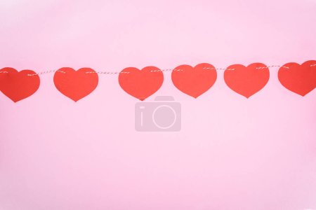 beautiful decorative red hearts hanging on rope on pink background, valentines day concept