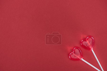 top view of two heart shaped lollipops on red background, valentines day concept