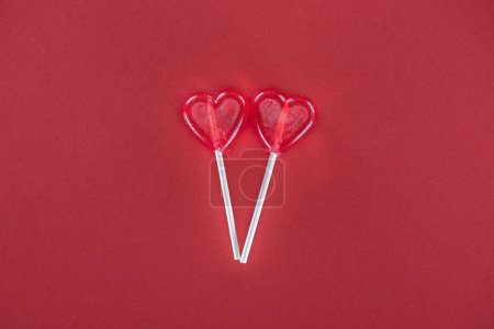 two heart shaped lollipops on red background, valentines day concept