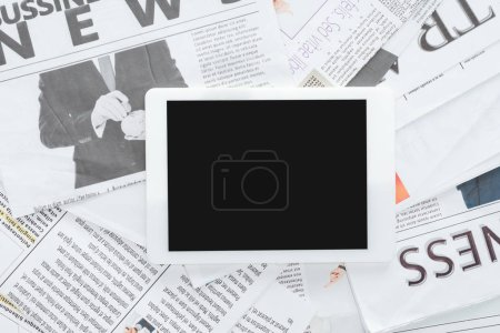 Photo for Top view of tablet with blank screen on business newspapers - Royalty Free Image