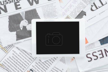 Photo pour Vue de dessus de tablette avec écran blanc sur les journaux d'affaires - image libre de droit