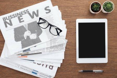 Photo pour Élevé de voir des plantes en pot, stylo, tablette avec écran blanc et journaux d'affaires sur une table en bois - image libre de droit