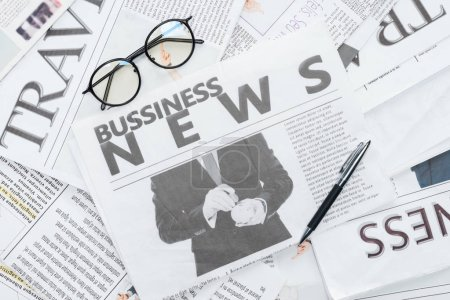 top view of eyeglasses and pen on business newspapers